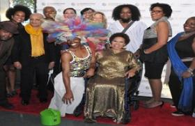 "Exhibition artists flock writer Ntozake Shange at opening reception of ""i found god in myself:"" the 40th anniversary of Ntozake Shange's for colored girls at the Schomburg Center. September 17, 2014. L to R: SOL'SAX, Pamela Council, Uday K. Dhar, Dianne Smith, Kathleen Granados, Melissa Calderon, Arlene Rush, designer Marco Hall, Kimberly Mayhorn, Nona Faustine, Michael Paul Britto, Beata Drozd Center: ​ Exhibit curator Souleo and Ntozake Shange (credit: Robert Gore) for Afrobeauty Article"