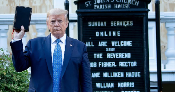 """Donald Trump holding a Bible, backward--which perhaps is a fitting metaphor for the hypocritical white conservative """"Christians,"""