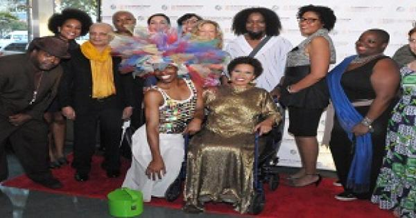 """Exhibition artists flock writer Ntozake Shange at opening reception of """"i found god in myself:"""" the 40th anniversary of Ntozake Shange's for colored girls at the Schomburg Center. September 17, 2014. L to R: SOL'SAX, Pamela Council, Uday K. Dhar, Dianne Smith, Kathleen Granados, Melissa Calderon, Arlene Rush, designer Marco Hall, Kimberly Mayhorn, Nona Faustine, Michael Paul Britto, Beata Drozd Center:  Exhibit curator Souleo and Ntozake Shange (credit: Robert Gore) for Afrobeauty Article"""